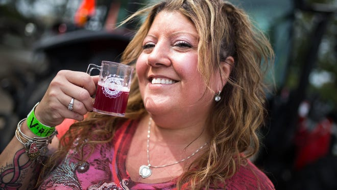 Shauna Chapman of Rockford shows off her tasting cup of Forest City Brewers' raspberry hefeweizen at the eighth annual Screw City Beer Festival on Sept. 8, 2018, at Riverview Ice House in Rockford.