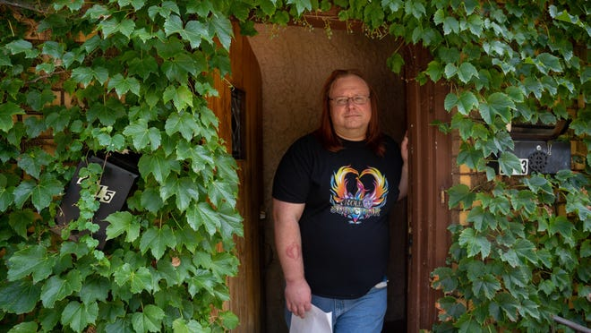 Travis Legge stands in his front door. The two addresses  on the building are covered by vines.