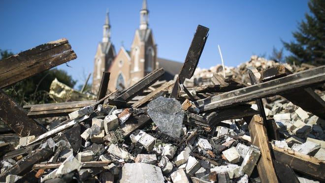 First Lutheran Church looms over the smoldering rubble at Rockford Masonic Cathedral on Thursday in Rockford, after a fire the previous evening destroyed the building, which dates to 1869.