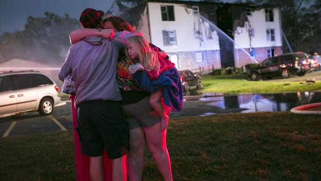 Jake Castro, left, hugs his cousin Savannah Perrin and her daughter, Iona, 2, as the Perrin's apartment building burns in the background Wednesday, Oct. 14, 2020, in Loves Park.