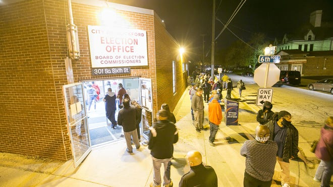 Voters stand in line just before polls close at 7 p.m. at the Rockford Board of Elections office, 301 S. Sixth St., on Tuesday in Rockford, Illinois.