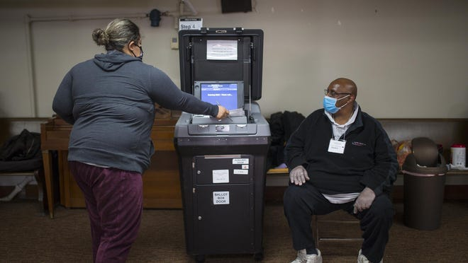Jennifer Ortiz of Rockford casts her ballot as election judge Johnnie McCoy monitors the ballot box at St. Paul Lutheran Church, 600 N. Horsman St., on Tuesday in Rockford.