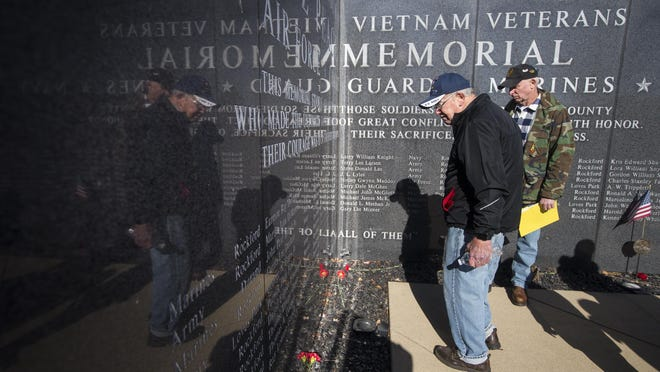 Navy veteran Arne Larsen of Rockford, left, shows Army veteran Chuck Larson his cousin's name on the LZ Peace Memorial after the Veterans Day ceremony on Wednesday, Nov. 11, 2020, in Rockford.