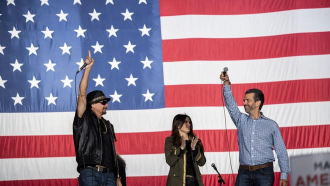Kid Rock, left, Trump campaign advisor Kimberly Guilfoyle and Donald Trump Jr. appear on stage Monday at a rally in Harrison Township, Mich.