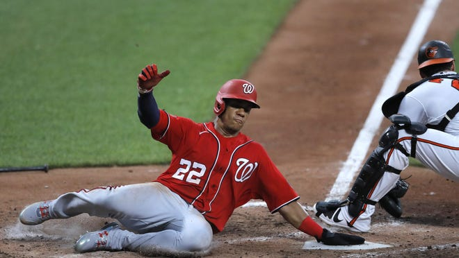 Washington Nationals outfielder Juan Soto slides in ahead of a tag by Baltimore Orioles catcher Austin Wynns during an exhibition game, Monday, July 20, in Baltimore.