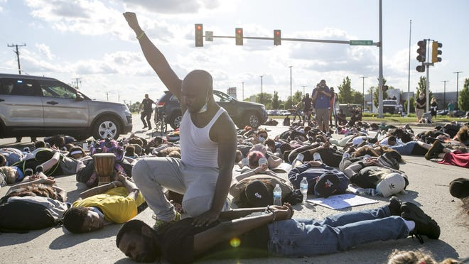 William Copeland, 29, of Rockford, kneels on Leslie Rolfe, of Rockford Youth Activism, at the intersection at East Riverside Boulevard and Perryville Road during a moment of silence for George Floyd, the man who was killed when police detained him for over eight minutes in this position. Rockford Youth Activism leads their fourth protest against police brutality at various locations on Friday, June 5, 2020, in Loves Park.