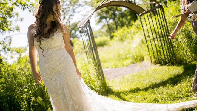 Paige Castro adjusts her gown during portraits with friends and family following her wedding ceremony with Jake Castro, not pictured, at Old Coon Creek Inn on Saturday, June 13, 2020, in Beloit.