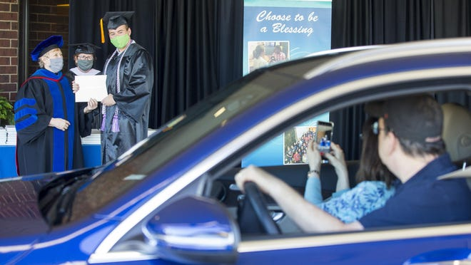 Jared Pape of Rockford, center, receives his bachelor of science in nursing diploma Friday as his parents, Sheri and Bruce, watch from their vehicle during the Saint Anthony College of Nursing drive-by graduation ceremony at the Tebala Event Center in Rockford. The event honored more than 100 graduates from December 2019 through May 2020.