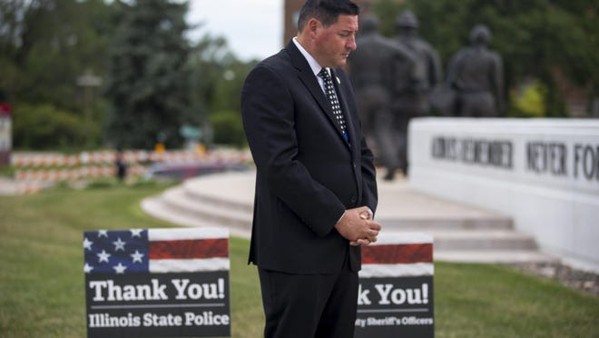 """State Rep. John Cabello, a Rockford police detective, bows his head in prayer Saturday during a """"Back the Blue"""" rally outside the Winnebago County Criminal Justice Center in Rockford."""