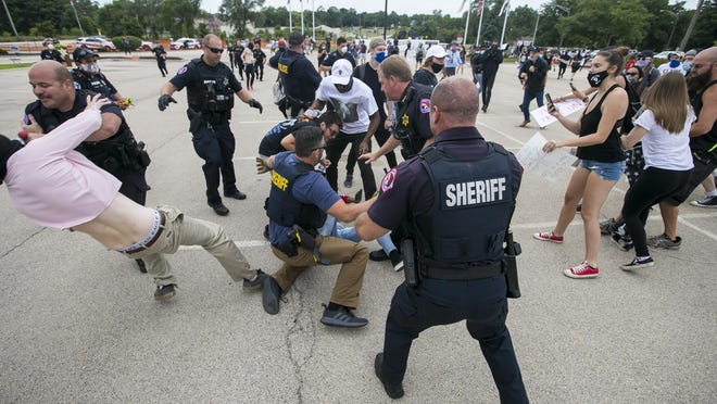 """Winnebago County sheriff's deputies and Rockford police converge on protesters after a """"Back the Blue"""" rally outside the Winnebago County Criminal Justice Center on Saturday in Rockford."""