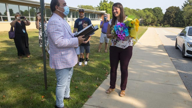 Sunil Puri, left, presents Erin Salberg, principal of Nashold Early Childhood Center, the Golden Apple for principals at Nashold Early Childhood Center on Wednesday in Rockford.