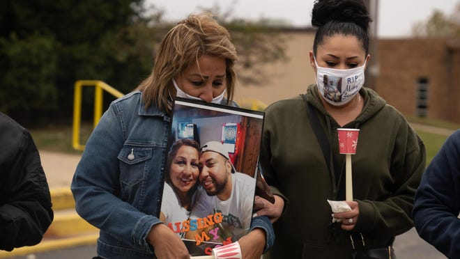 Juanita Eslora hugs a picture of her and her son Michael Guzman before she addresses the crowd near Saint Peters Roman Catholic Church on Saturday in South Beloit.