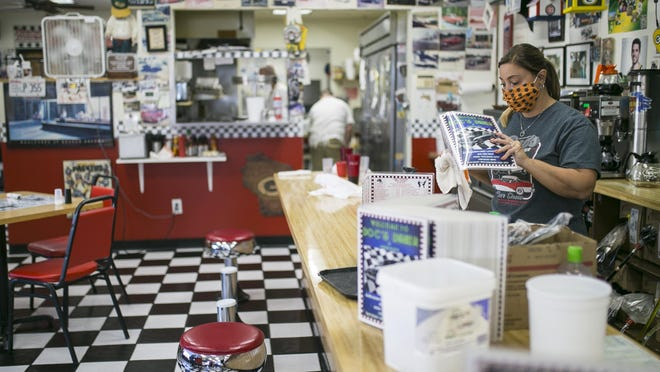 Jenifer Nordheim, a server for 24 years, sanitizes menus between customers at Doc's Diner on Thursday, Oct. 15, 2020, in Loves Park. The restaurant has received an order of closure but says it plans to stay open.