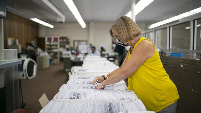 Stacey Bixby, Rockford Board of Elections executive director, looks at the 14,000 mail ballot applications received from voters at the Rockford Board of Elections office on Sept. 2 in Rockford.