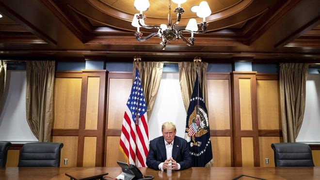 In this image provided by the White House, President Donald Trump listens during a phone call with Vice President Mike Pence, Secretary of State Mike Pompeo, and Chairman of the Joint Chiefs of Staff Gen. Mark Milley, Sunday, Oct. 4, 2020, in his conference room at Walter Reed National Military Medical Center in Bethesda, Md. White House chief of staff Mark Meadows was also in the room, but not pictured, according to the White House.