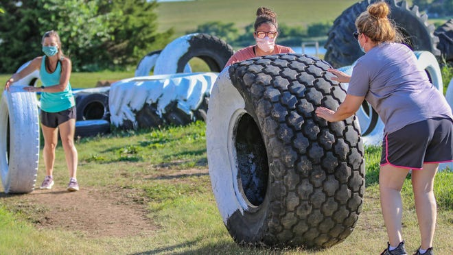Holly Hartman, fifth-grade teacher; Stephanie Markle, parent and president of the Playground Committee, and Stephanie Harris, first-grade teacher, move the tires from the staging area to their new location in the new playground area at Southeast of Saline School on Wednesday evening.