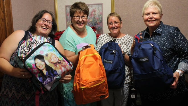 From left: Sister Sarah Ganser, Sister Denise Schmitz, CSJ Candidate Angela Jones and Sister Dian Hall help prepare backpacks with personal items before they will be sent to western Kansas in October to help foster children in need.