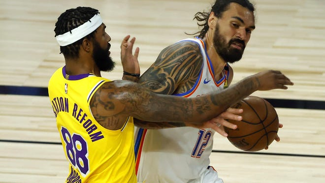 Steven Adams, of the Oklahoma City Thunder, is defended by Markieff Morris, of the Los Angeles Lakers on Wednesday in Lake Buena Vista, Fla.