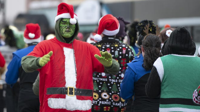 The Grinch helps direct the Hutchinson High School band while it marched in the Christmas Parade in 2018.