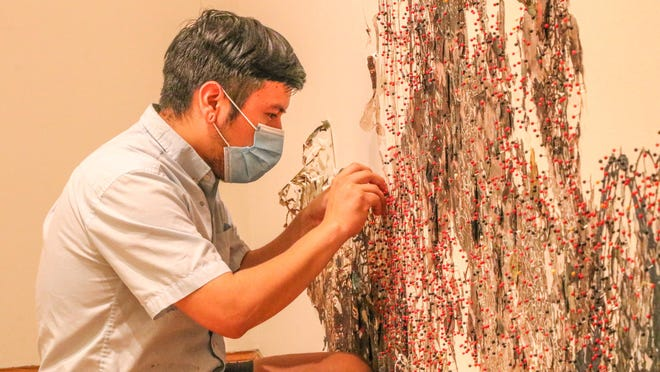 Artist Fidencio Fifield-Perez, of Columbia, Mo., applies red and black push pins on his artwork at the Salina Arts Center, 242 S. Santa Fe Ave., during the surge installation on Friday.