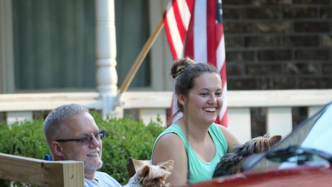 Pastor Kent Happel and his daughter, Tori Happel, watch  the drive-by parade bidding the pastor farewell outside their residence on Friday evening.