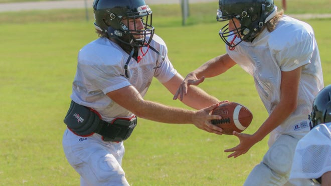 Ell-Saline quarterback TJ Morrical, left, hands the ball off during Tuesday's practice in Brookville.