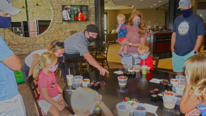 Bradley Smith, Salina Country Club executive sous chef, points to the dirt and worms he made and explains what each layer is made  of during the Kid's Cooking with Chef event at Salina Country Club on Saturday. Seven children enjoyed Shirley Temple drinks while making their desserts.
