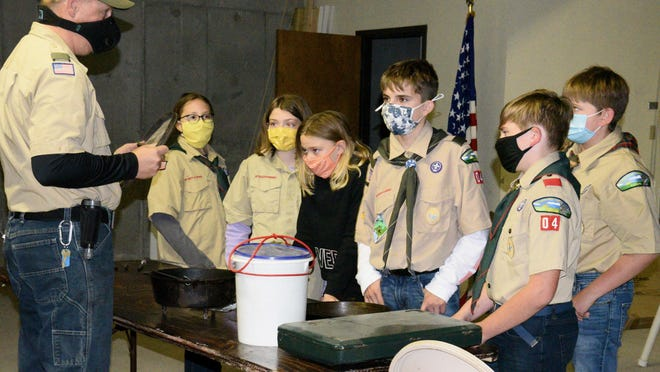 Boys and girls of Troop 1 and 1G learn from Troop 1 Scoutmaster Allen Holle about cast iron skillets and Dutch ovens. The focused Monday night on preparing for outdoor survival.