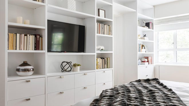 A wall of built-ins in a master bedroom provides additional storage.
