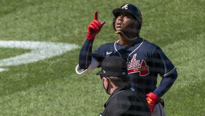 Atlanta Braves' Ozzie Albies, top, gestures as he rounds bases after hitting a two-run home run during the sixth inning of a baseball game against the Washington Nationals in Washington, Sunday, Sept. 13, 2020.