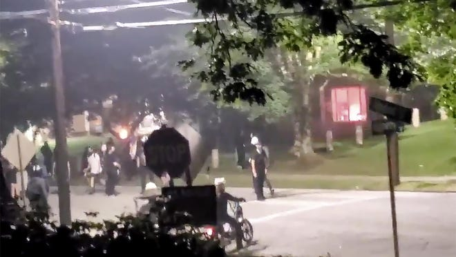 The building, seen right in the background, that houses Georgia State Patrol headquarters is vandalized in Atlanta, Sunday, July 5, 2020. Video showed protesters appearing to set off at least one firework inside the building.