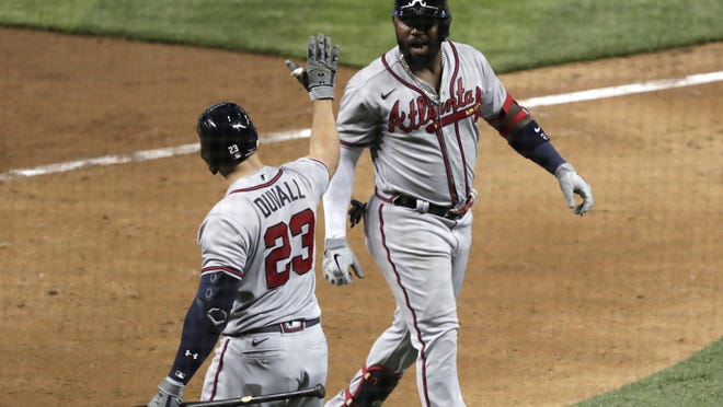 The Atlanta Braves' Marcell Ozuna, right, is met by Adam Duvall (23) after scoring on a solo home run during the seventh inning against the Miami Marlins on Saturday night in Miami.
