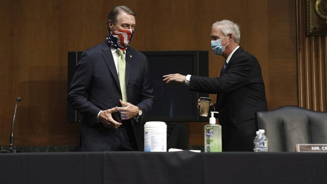 Sen. David Perdue, R-Ga., speaks to Sen. Ron Johnson, R-Wis., before a Senate Foreign Relations committee hearing on the State Department's 2021 budget on Capitol Hill Thursday, July 30, 2020, in Washington.