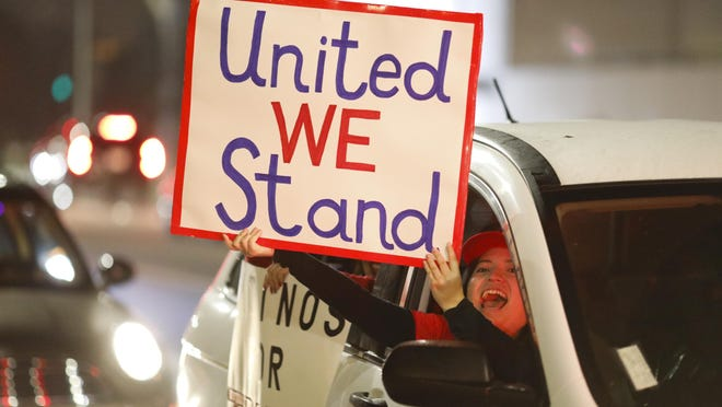 A woman holds a sign in her car during a protest on Election Day.
