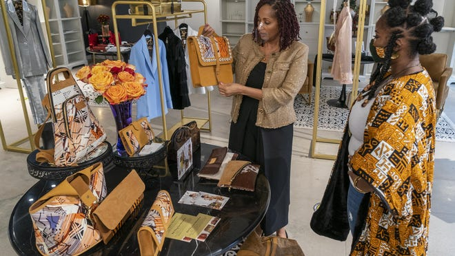 Store founder Sheila Hawkins-Bucklew, center, speaks about a handbag from House of Takura with creative director Helen Annette Njau, right, inside Showroom 808. The store in the Domain Northside focuses on jewelry and clothing by women of color and female entrepreneurs.