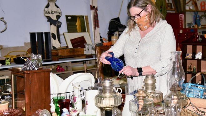 Vicki Bethe examines an item for sale at her booth during the Gypsum Flee Market on Thursday evening. Bethe was one of seven vendors who had items for sale at the flea market that was part of the 4th Annual Last Chance Christmas Shopping Vendor Fair.