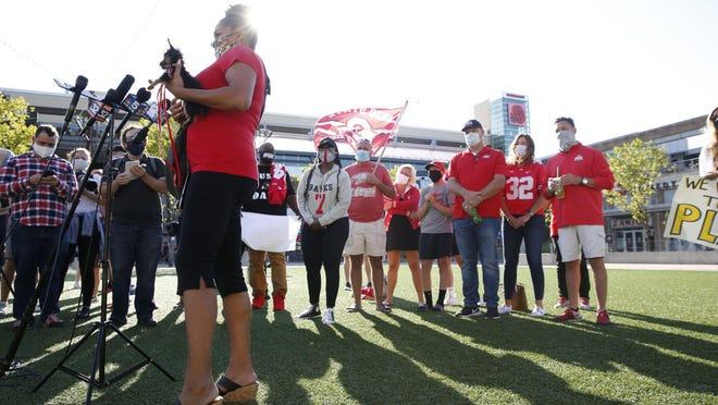 Holding her dog, Sadie, Ohio State football parent Candace Wilson speaks during a news conference asking for more transparency and communication by the Big Ten outside of their headquarters in Rosemont, Illinois, on  Aug. 21. Parents from Ohio State, Iowa and Wisconsin were just some on hand for the protest.