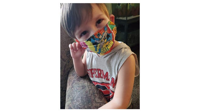 """Cooper Stuck, 6, an incoming kindergartner wears a Batman mask made by his mother, Shayne Stuck. """"I've been making kids face masks since March,"""" Stuck said."""