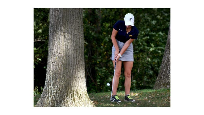 Payton Bucki of Airport chips out of the trees during a match at Sandy Creek Golf Course.