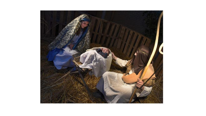 St. Patrick Catholic School eighth-graders Hannah Roof as Mary and Noah Iott as Joseph pay attention to three-month-old Waylon Hegedus as baby Jesus in the third live nativity event at the Divine Grace Parish in Carleton Saturday.