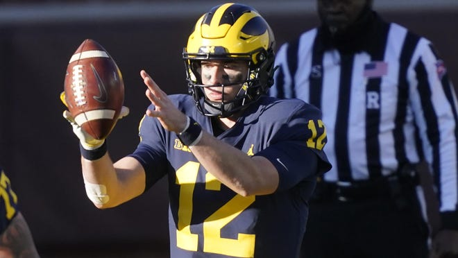 Michigan quarterback Cade McNamara takes the snap during the second half of an NCAA college football game against Penn State, Saturday, Nov. 28, 2020, in Ann Arbor, Mich.
