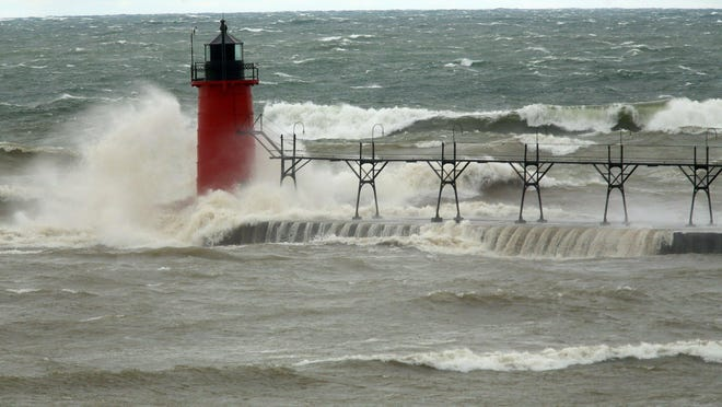 In this April 6, 2017, file photo, strong winds send huge waves at the Lake Michigan shoreline at South Haven. A decade-old program that has pumped $2.7 billion into healing long-term injuries to the Great Lakes environment has received authorization from Congress to continue another five years. The U.S. Senate voted unanimously Sunday, Dec. 20, to extend the Great Lakes Restoration Initiative, which the House did earlier this year.