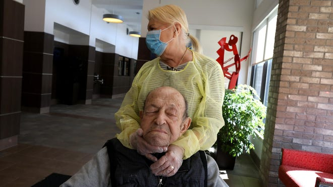 Johanna Mannone, of Rochester Hills, caresses her husband Michael Mannone at WellBridge nursing and rehabilitation center in Rochester Hills on Friday, March 13, 2020.  The state's nursing homes are seeing an increase in coronavirus cases and deaths among residents and staff, and several groups are sounding the alarm.