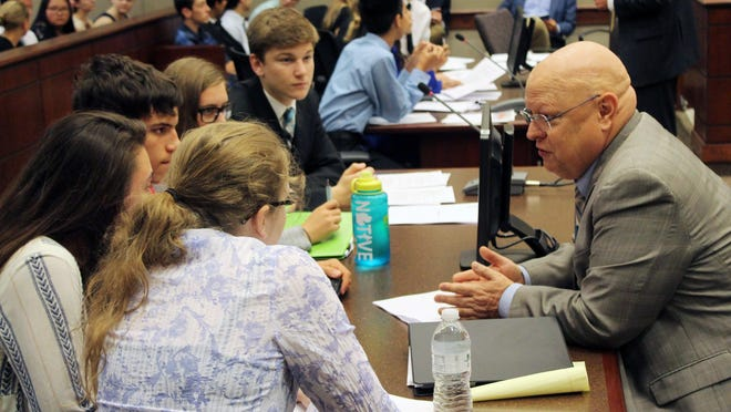 """Attorney Bob Hamilton, right, speaks to a team of Holland High School students during a 2016 """"mock trial"""" in Holland district court. Hamilton was named Ottawa County public defender in 2018, overseeing legal counsel in the county for those who cannot fully afford it."""