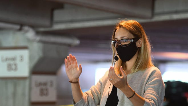 Donned in a mask and safety glasses, Jennifer Heder, a first year doctoral student in choral conducting leads rehearsal with fellow graduate students from MSU's College of Music Wednesday, Sept. 23, 2020, in the Kellogg Center parking garage.