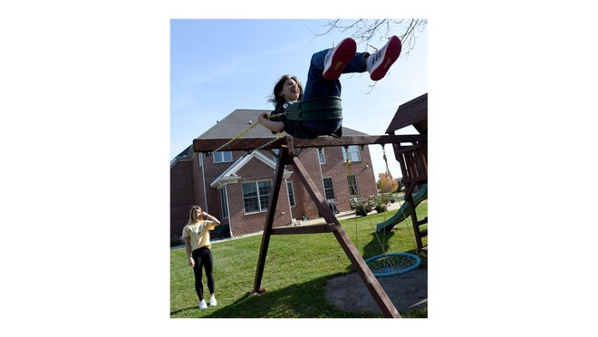 Caroline Lipford, 13, gets a push from her older sister Grace, a 17-year-old senior at St. Mary Catholic Central, during unseasonably warm weather in Monroe during the weekend. Caroline, a  fifth grader at Raisinville Elementary who is autistic, loves to swing and go high.