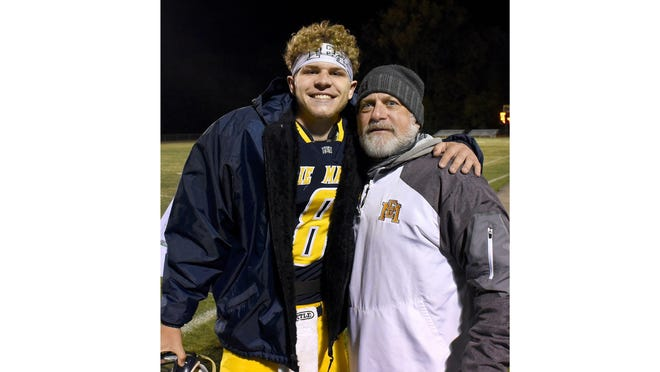 Erie Mason football coach Rob Beaudrie (right) hugs his son, Noah, after the school's first playoff win since 2003.