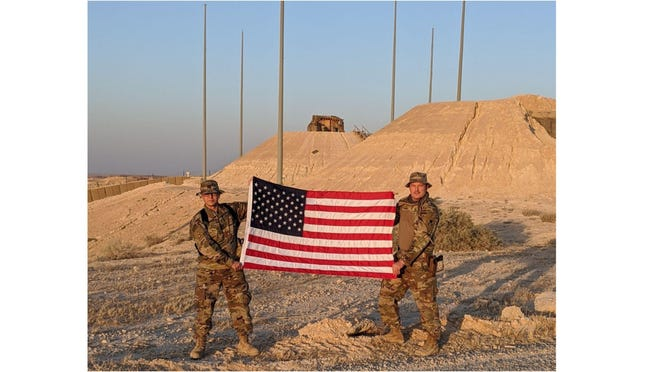 William Bruck of Erie, a U.S. Army Reserve Chief Warrant Officer 3, and his buddy, hold an American flag in the Middle East. Bruck is spending Christmas deployed overseas, away from his wife, Natalie, and nine children.