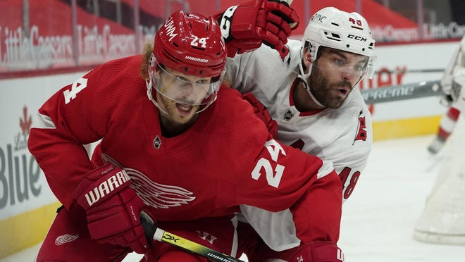 Detroit Red Wings' Jon Merrill (24) and Carolina Hurricanes left wing Jordan Martinook (48) battle for position in the third period of an NHL hockey game Thursday, Jan. 14, 2021, in Detroit.