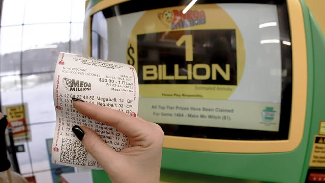A patron, who did not want to give her name, shows the ticket she had just bought Friday for the Mega Millions lottery drawing at the lottery ticket vending kiosk in a Smoker Friendly store in Cranberry Township, Pa. The jackpot for the Mega Millions lottery game grew to $1 billion ahead of Friday night's drawing.